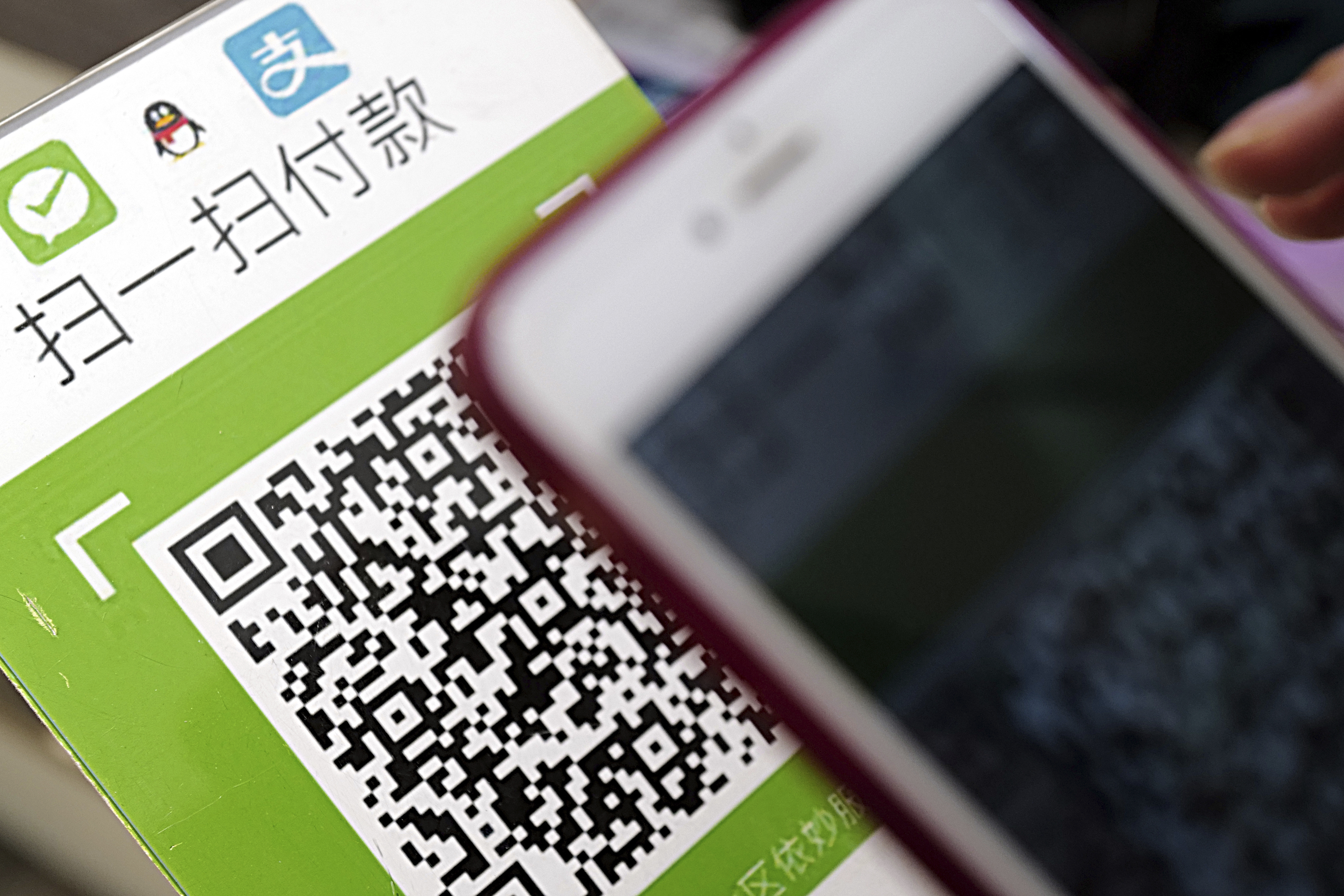 A Chinese mobile phone user scans a QR code via mobile payment service WeChat Pay of Tencent to pay his purchase.