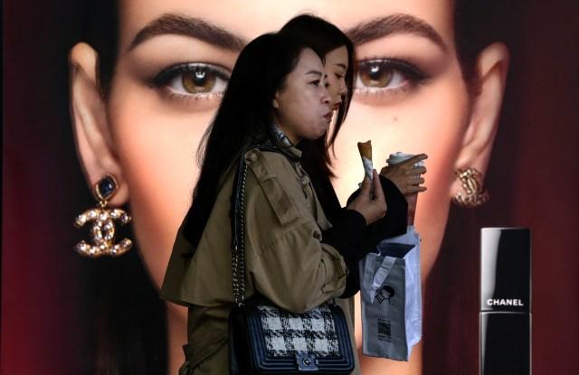 Women pass by a Chanel advertisement in Beijing.