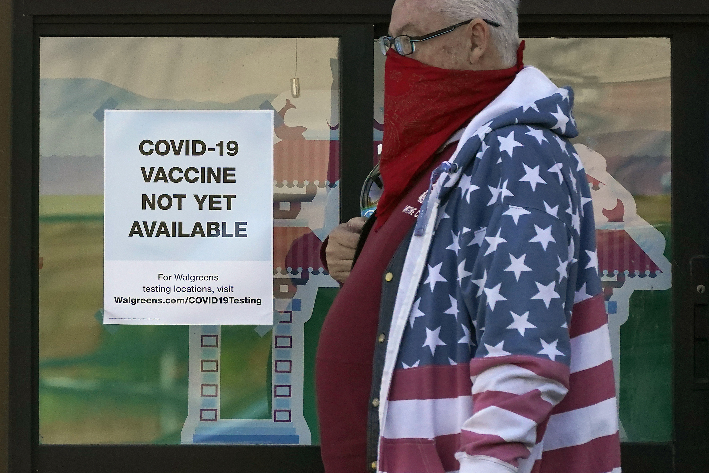 A pedestrian wearing a mask walks past a sign advising that COVID-19 vaccines are not available yet at a Walgreen's pharmacy store during the coronavirus outbreak in San Francisco, Wednesday, Dec. 2, 2020. (AP Photo/Jeff Chiu)