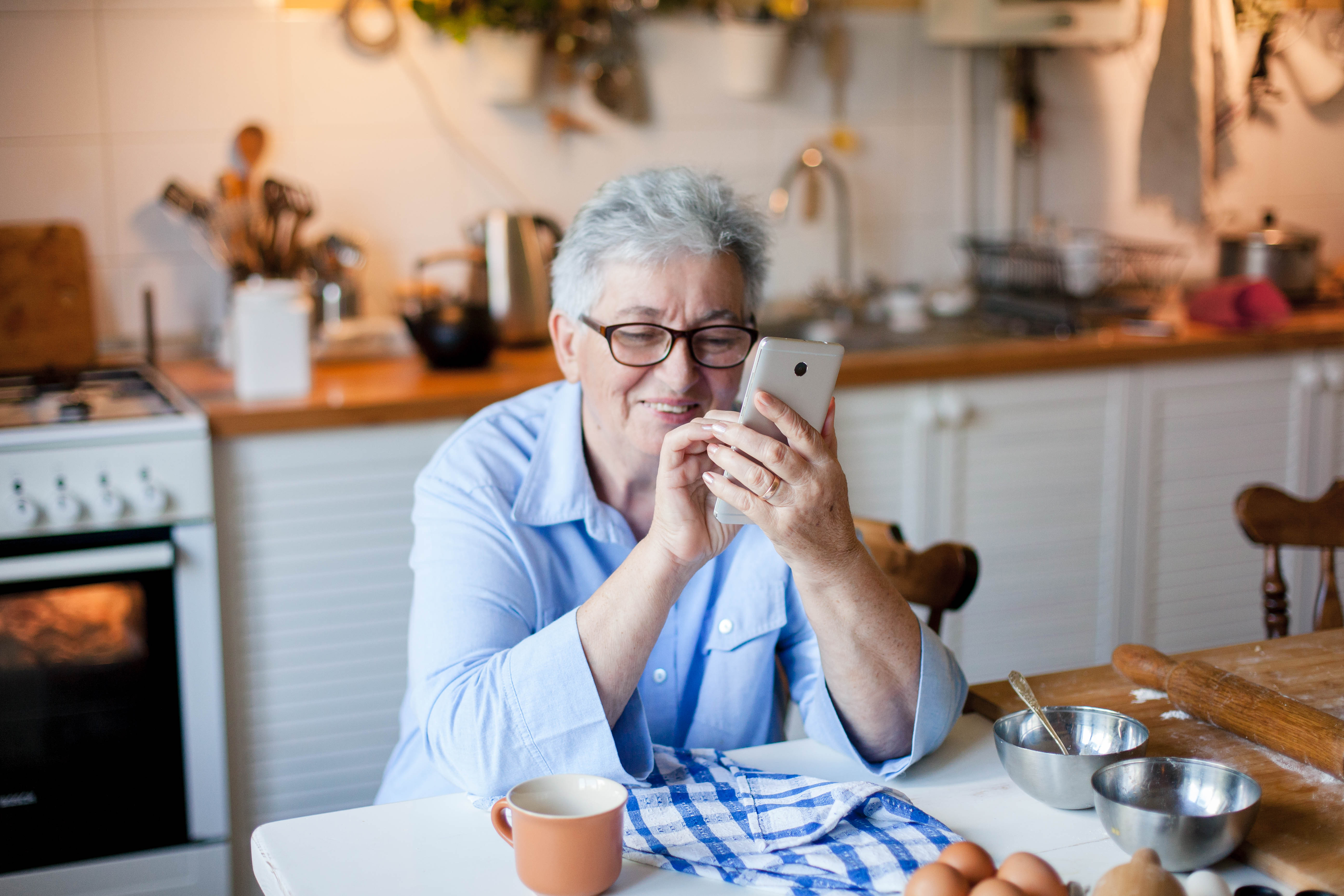 Senior woman using mobile phone at cozy home kitchen. Retired person shopping online. People connection, communication with gadget, delivery in isolation, distance healthcare. Lifestyle moment.