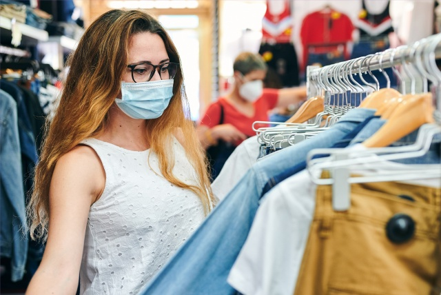 Woman in a safety mask looking at clothes in a shop. New post covid-19 normality