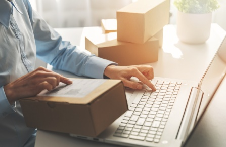 person preparing online store orders for shipping using laptop