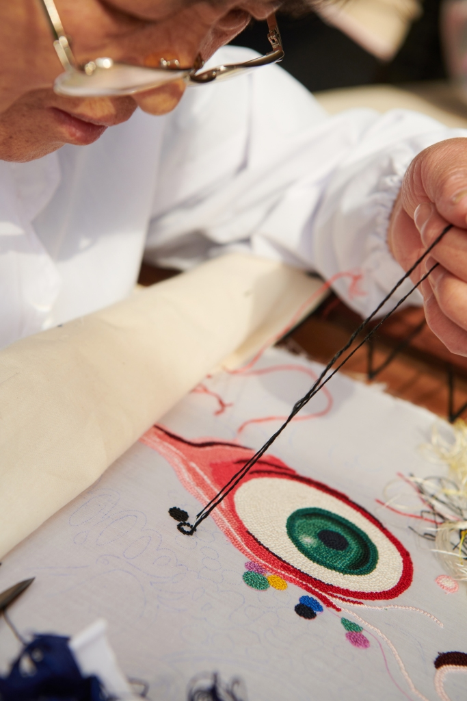 A worker embroiders Kenny Scharf's art work for the Dior pre-fall men's collection.