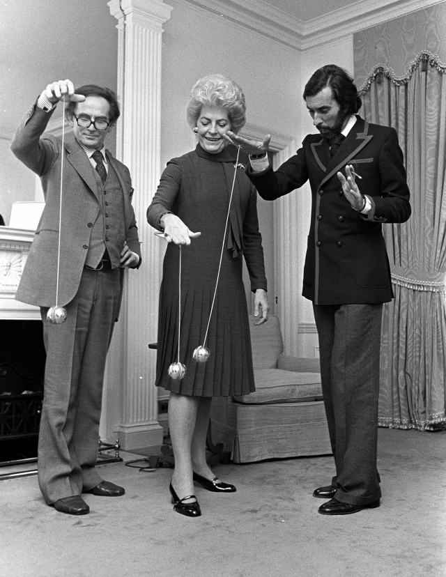Fashion designer Pierre Cardin playing with the yo-yo packaging that is included with his perfume, Cardin is accompanied by Nicole Alphand and Andre Oliver at the Hotel Pierre in New York