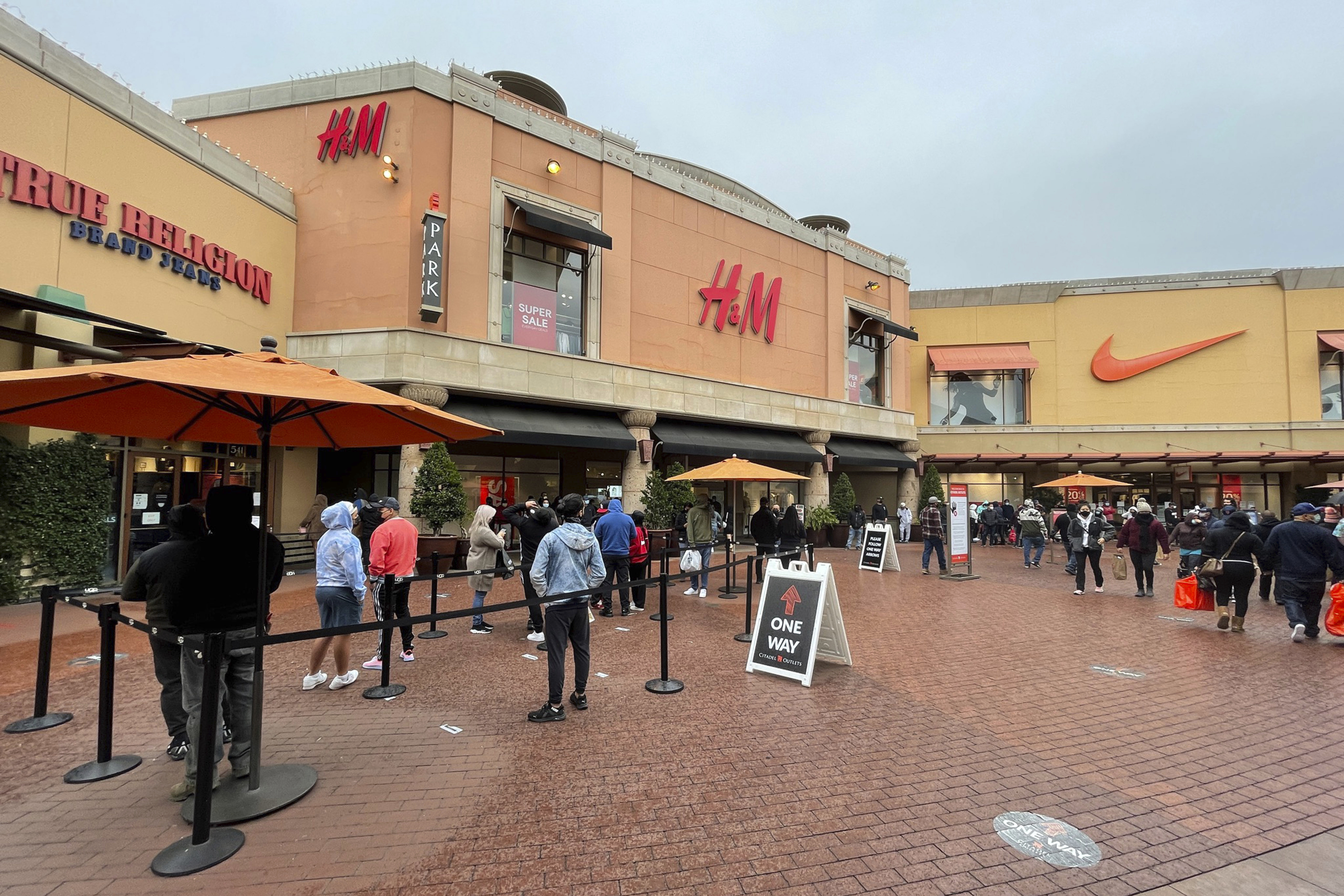 People stand in line outside the True Religion Brand Jeans, H&M and Nike stores the day before Christmas at the Citadel Outles un Los Angeles.