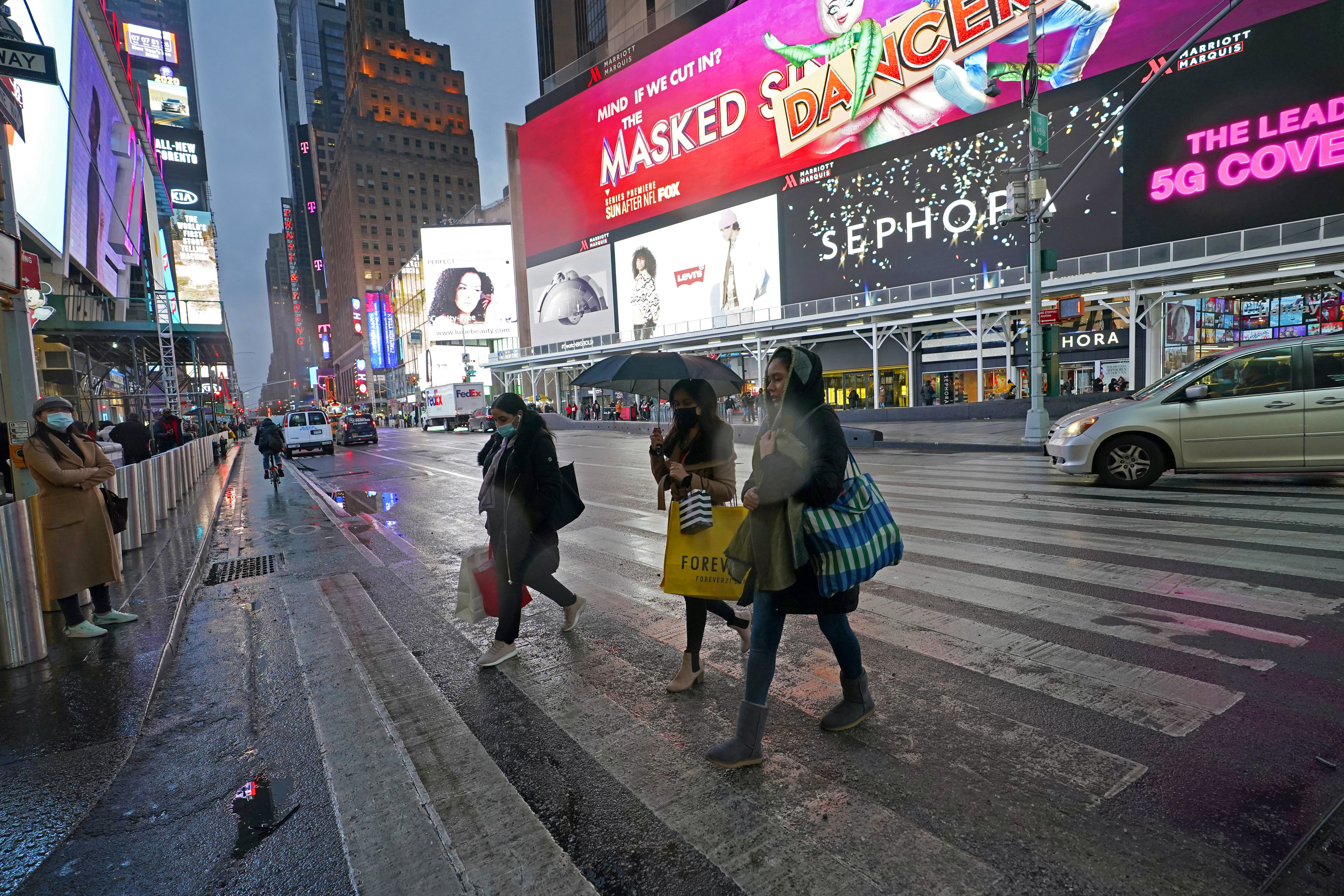 Shoppers walk across a nearly empty street on Christmas Eve in New York.