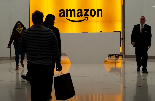 People walk into the lobby for Amazon offices in New York.