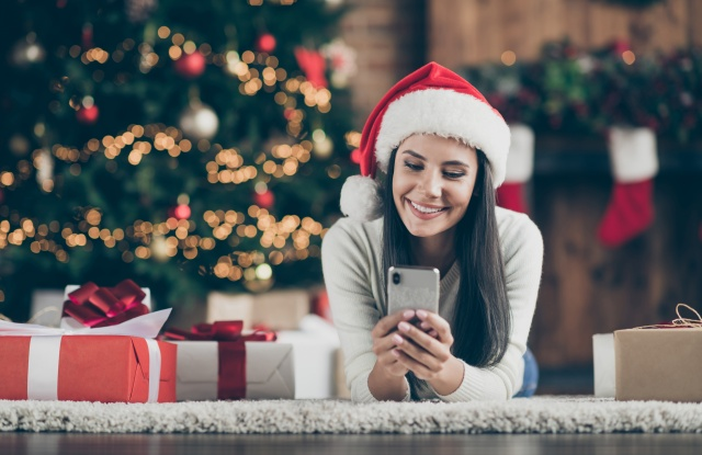Close up photo of positive girl in santa claus hat lie on carpet use smartphone send christmas, congratulation search discounts in house with x-mas comfort atmosphere indoors
