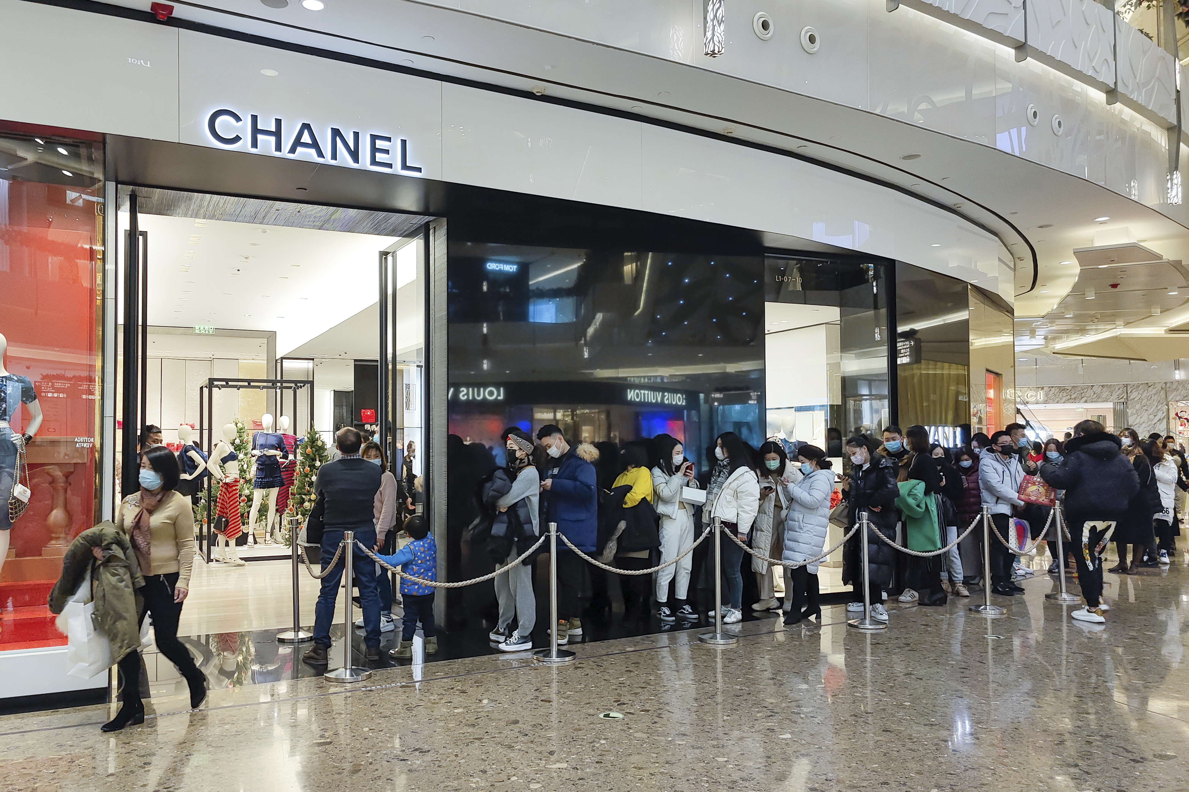 Shoppers line up outside a Chanel store in Shanghai, China on the last day of 2020.