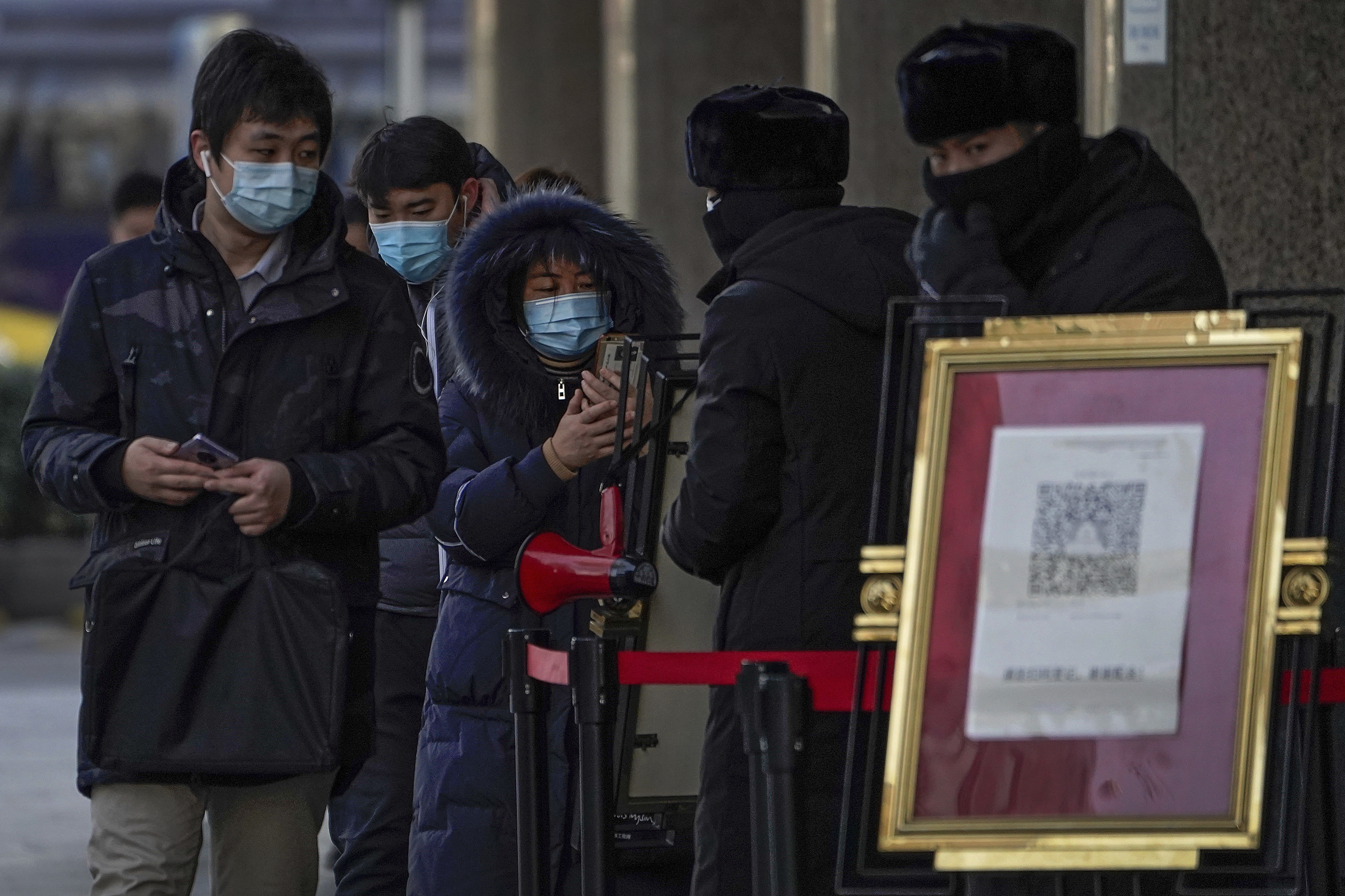 People wearing face masks to help curb the spread of the coronavirus use smartphones to scan their health code before entering an office building in Beijing.