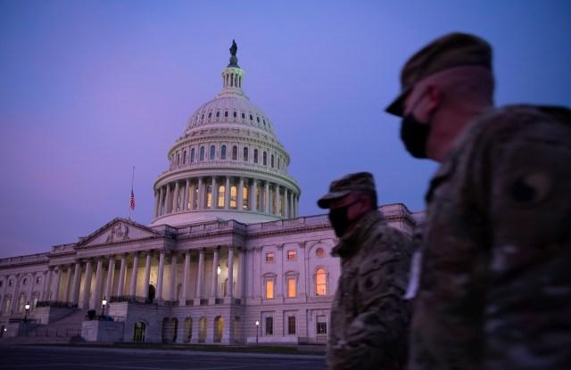 Members of the U.S. National Guard walk past the U.S. Capitol Building ahead of Inauguration in Washington, D.C., on January 15, 2021, amid the coronavirus pandemic. More than 20,000 members of the U.S. National Guard are stationed in Washington in the lead up to President-Elect Joe Biden's inauguration. (Graeme Sloan/Sipa USA)(Sipa via AP Images)