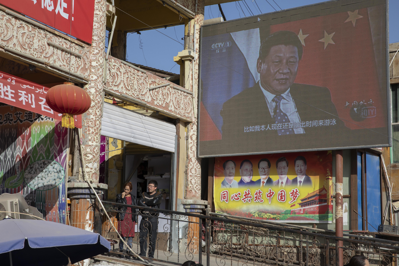 Chinese President Xi Jinping is seen on a screen in a Xinjiang bazaar.