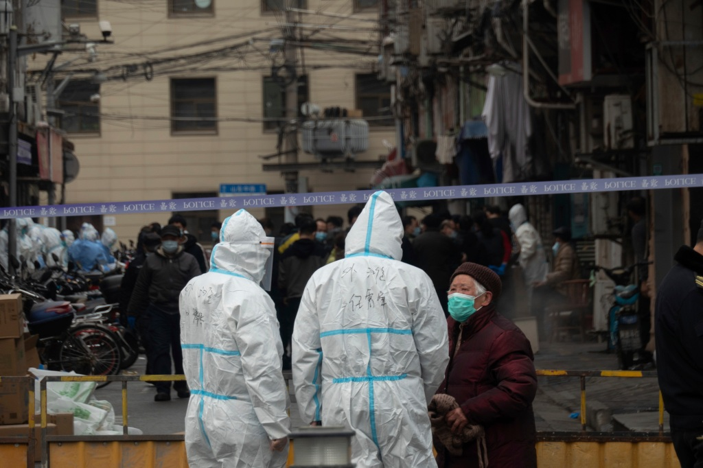 Government workers lock down a neighborhood in Huangpu district, the center of Shanghai, China Thursday, after a worker at a hospital found suspected of COVID-19 during a routine coronavirus test. Three new covid-19 cases were confirmed in the neighborhood by Thursday morning.