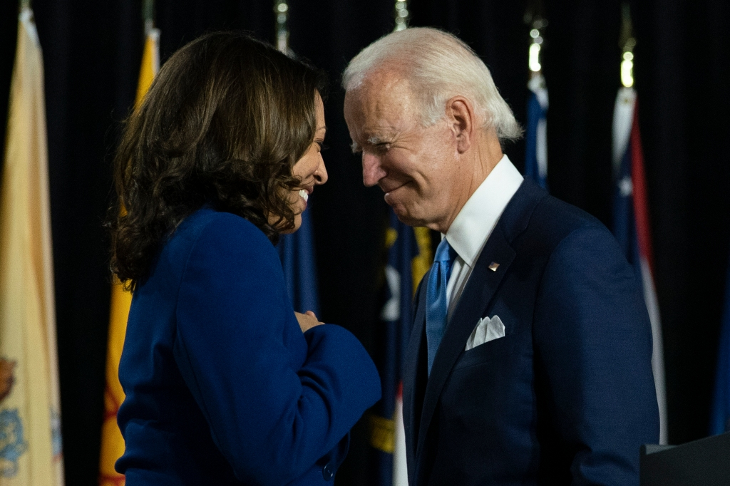 President-elect Joe Biden and his running mate Sen. Kamala Harris, pass each other as Harris moves to the podium to speak during a campaign event .