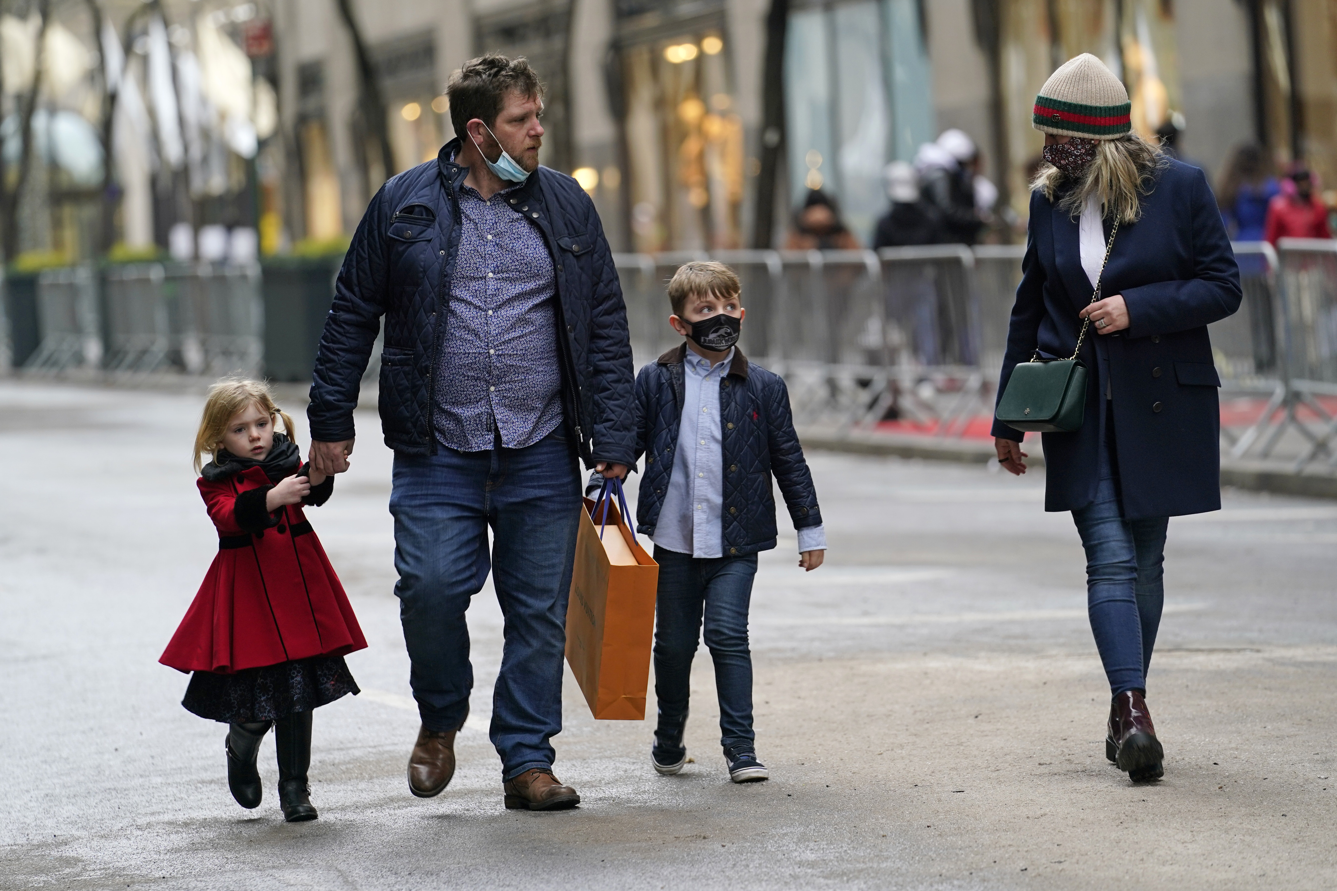 People walk down an empty street after shopping on Christmas Eve, Thursday, Dec. 24, 2020, in New York. (AP Photo/Kathy Willens)