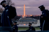 The Washington Monument and the National Mall are visible as members of the U.S. Air Force Honor Guard walk along the West Front of the U.S. Capitol.