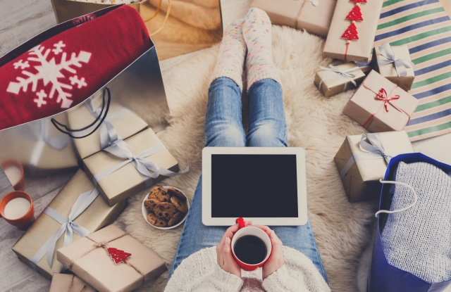 Christmas online shopping top view. Female buyer touch screen of tablet, copy space. Woman has coffee, buys presents, prepare to xmas eve, sitting among gifts boxes and packages. Winter holidays sales