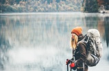 Woman with backpack hiking Lifestyle adventure concept forest and lake on background active vacations into the wild