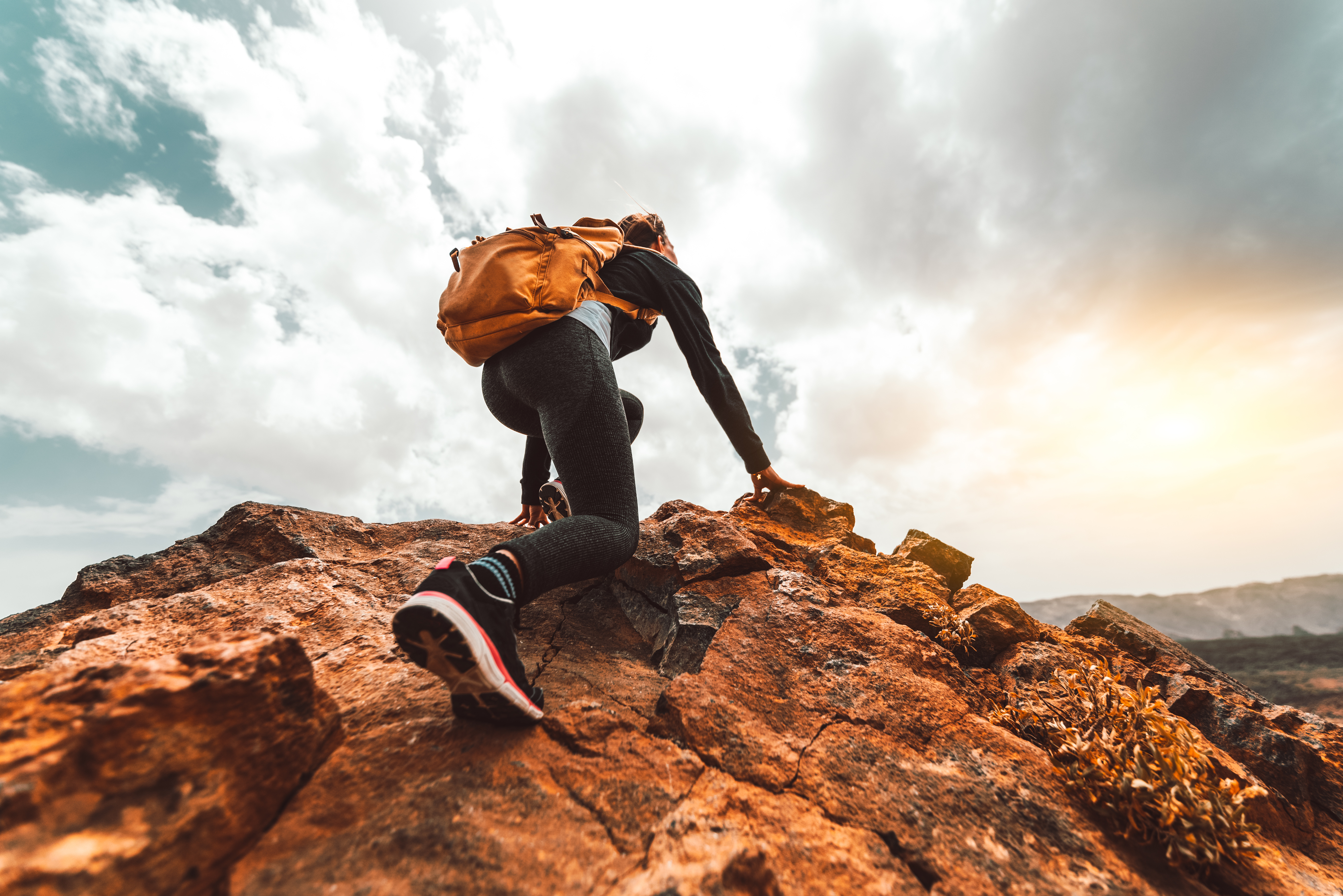 Success woman hiker hiking on sunrise mountain peak - Young woman with backpack rise to the mountain top. Discovery Travel Destination Concept