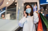 young woman talking with mobile phone in shopping mall and wearing face mask protective for spreading of coronavirus(covid-19) pandemic, new normal concept