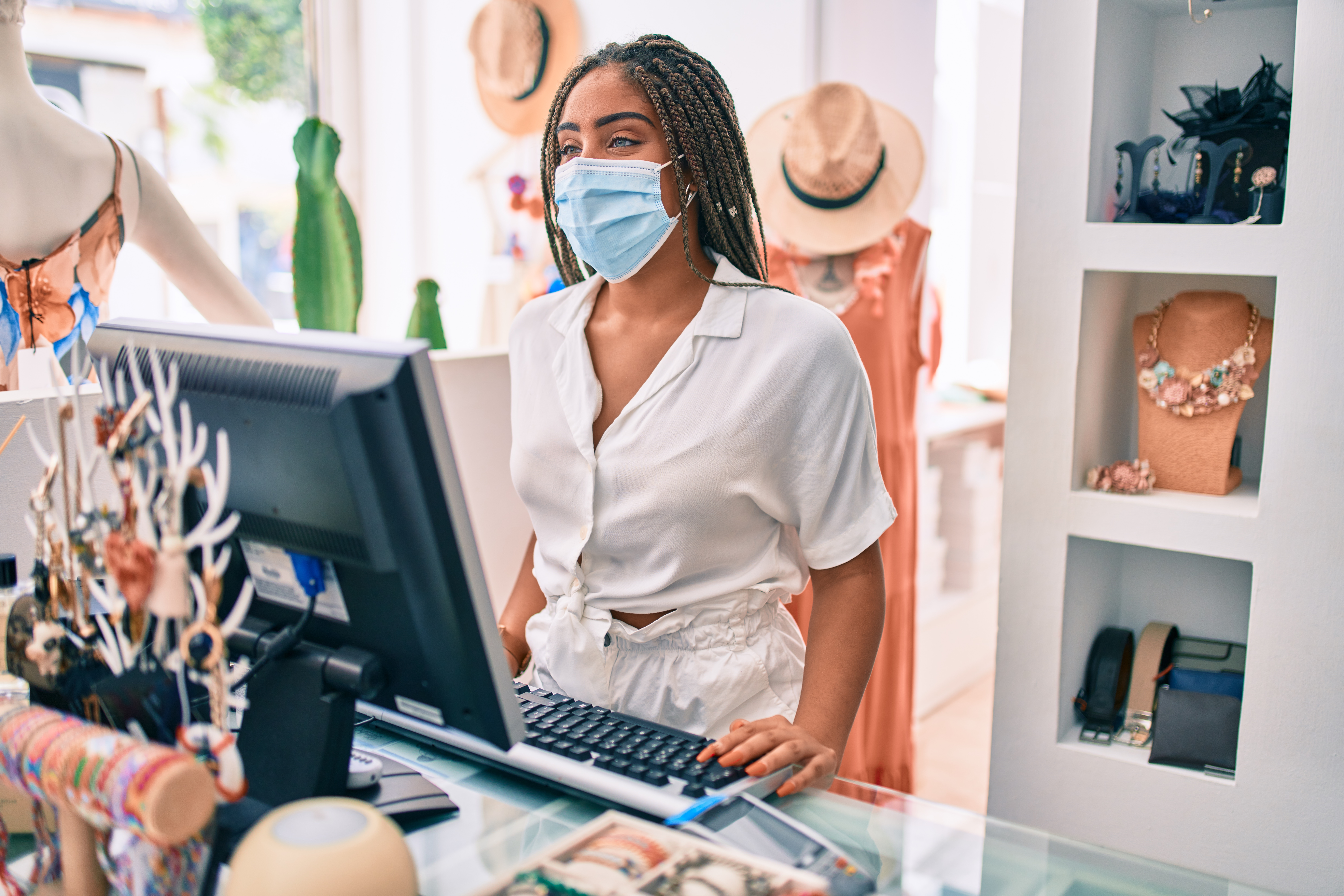 clothing store sales associate in mask at cash register