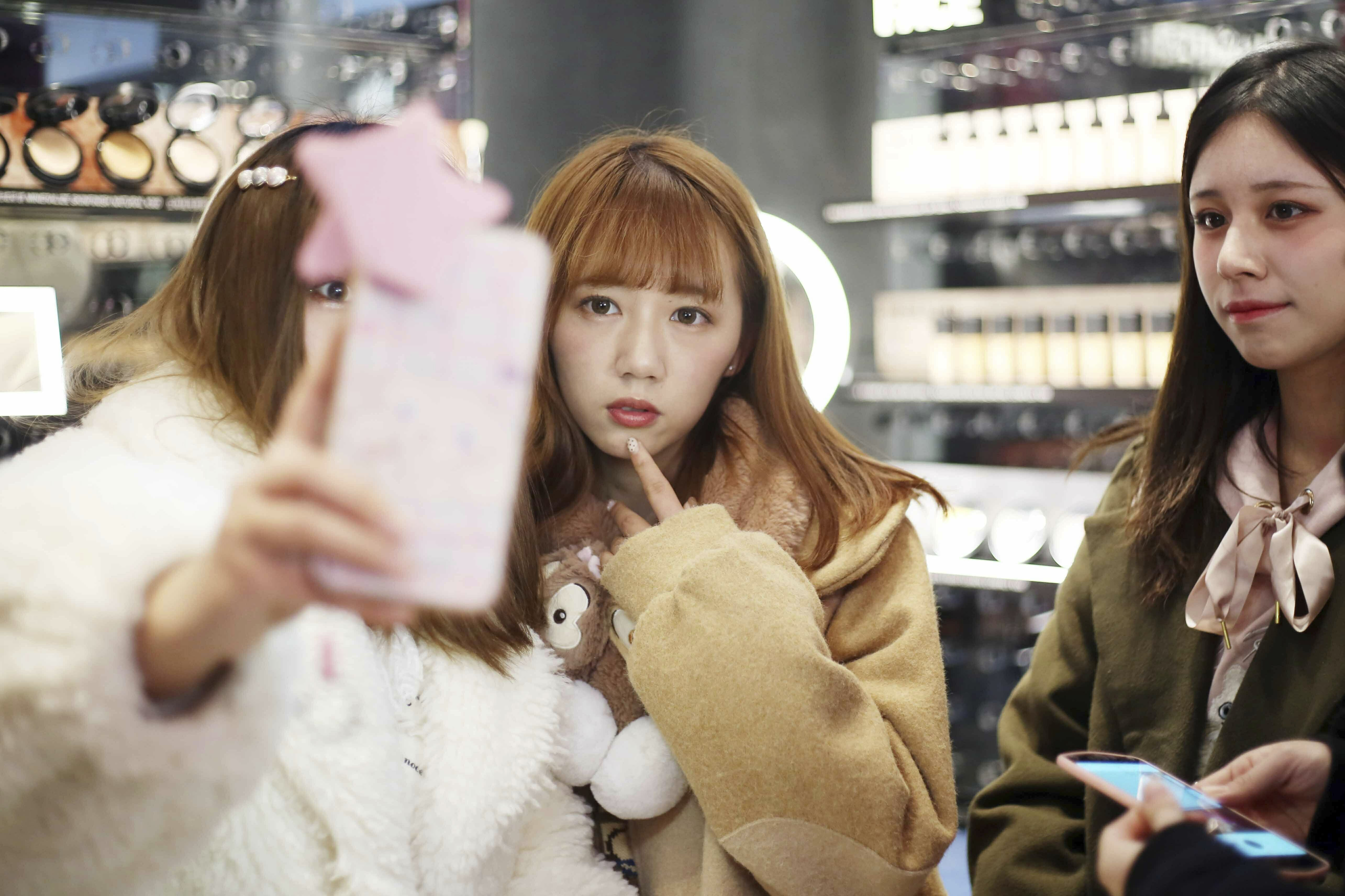 """Customers pose for selfies at the Huaihai Road flagship store of makeup brand MAC Cosmetics themed on Tencent's MOBA """"King of Glory"""" in Shanghai, China, 17 January 2019. The Huaihai Road flagship store of makeup brand MAC has been changed into a store themed on Tencent's MOBA 'King of Glory'. Themed limited lipstick collections are launched at the store.  (Imaginechina via AP Images)"""
