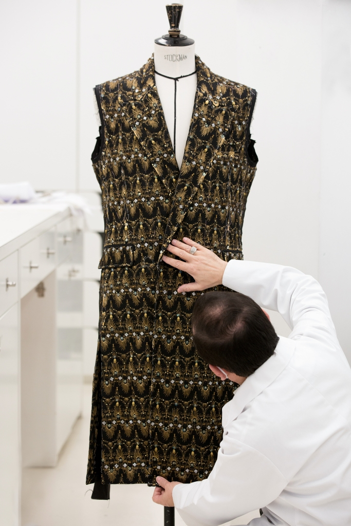 The black Dior Men's coat covered in a dense gold and rhinestone pattern.