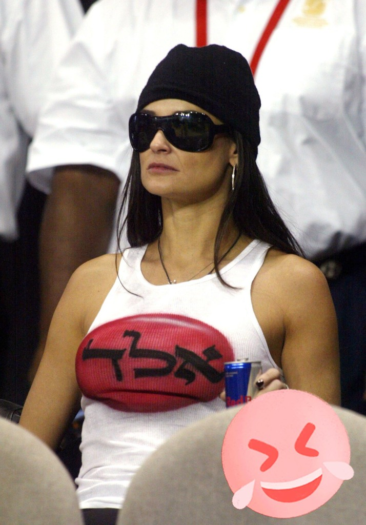 Demi Moore wears sunglasses and a black hat while watching the NBA All-Star game in Los Angeles, 2004.