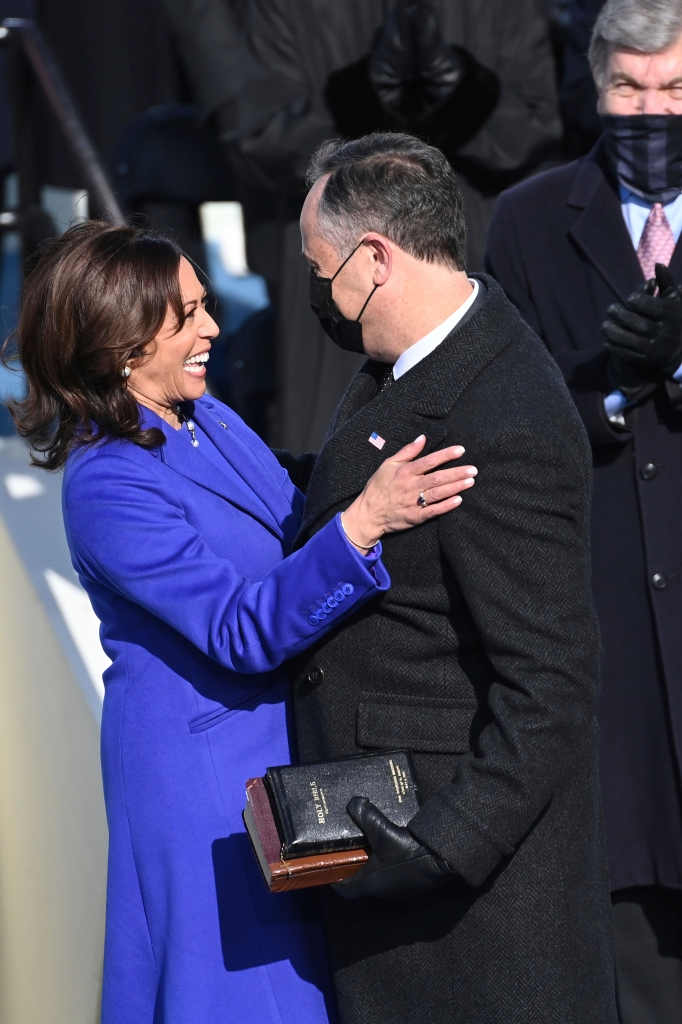Vice President Kamala Harris, wearing Christopher John Rogers and Sergio Hudson, is embraced by her husband Doug Emhoff.