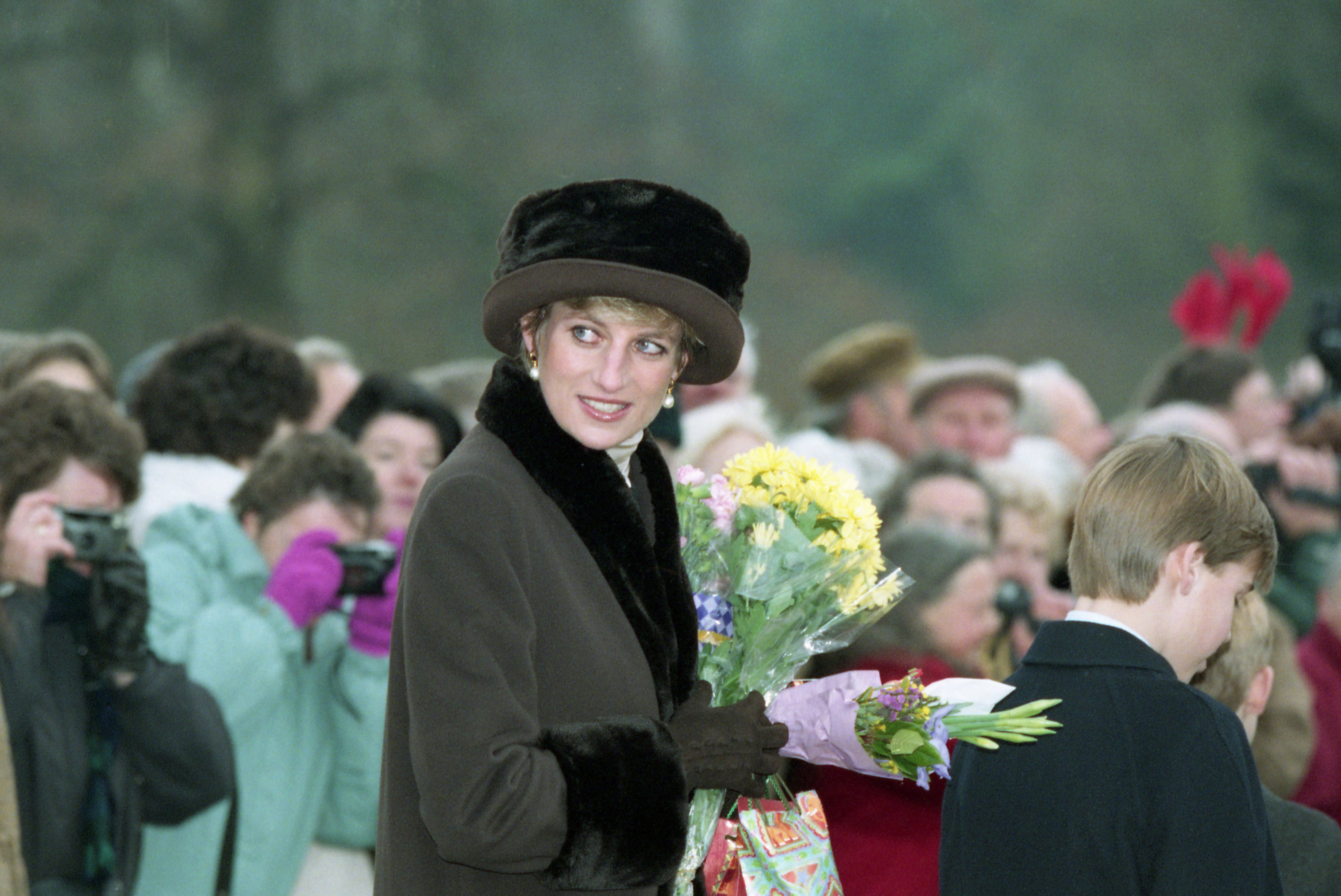 Princess Diana, the Princess of Wales, with flowers and Christmas presents she received from the public outside the Sandringham Church, England, after the Christmas Day service on Dec. 25, 1994. The Princess attended the service with the rest of the British Royal family and several hundred people lined the road outside the Church to bid the Royal family happy Christmas. (AP Photo/Max Nash)