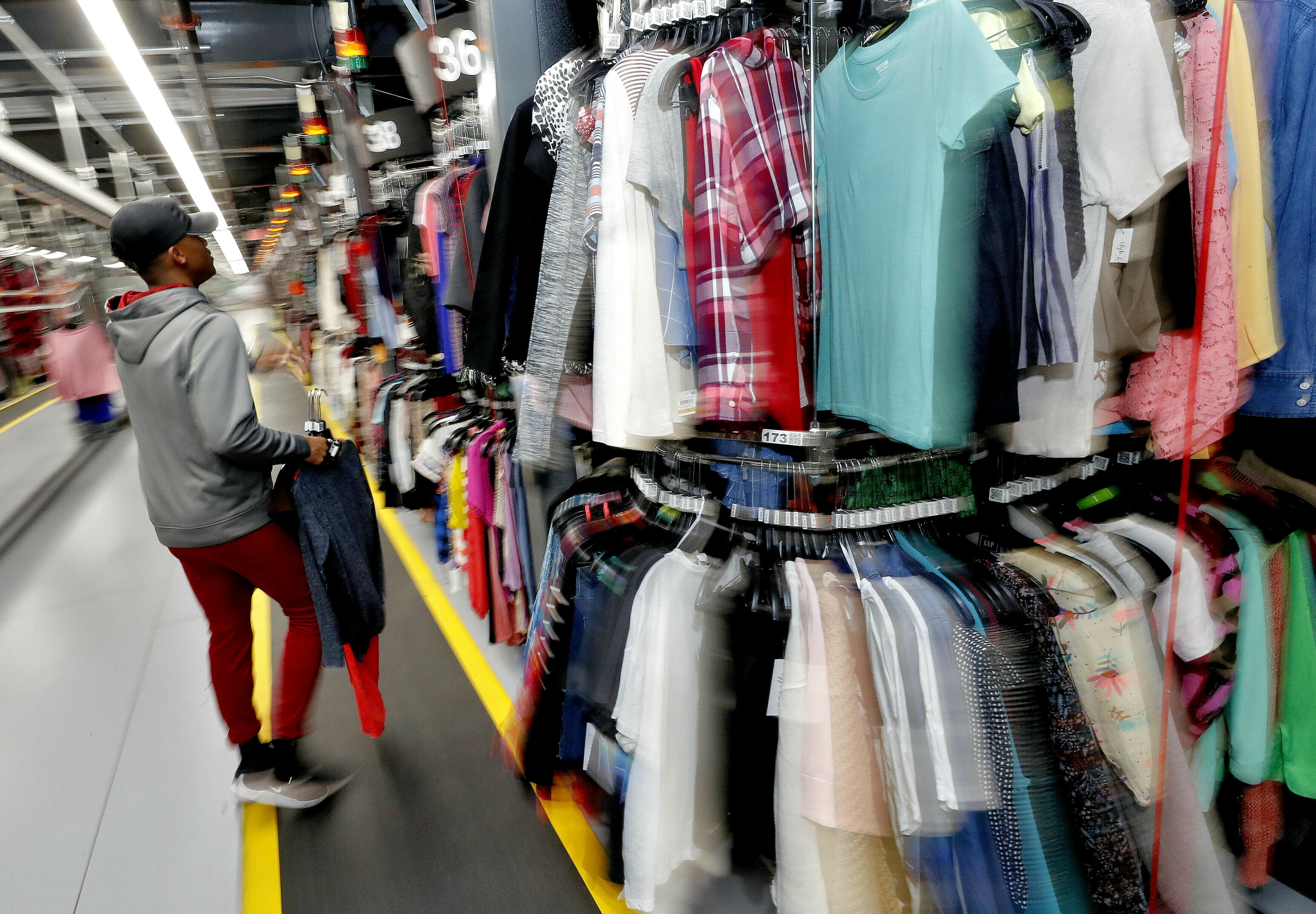FILE - In this March 12, 2019, file photo Willie Walton hangs clothing on a three-tiered conveyor system at the ThredUp sorting facility in Phoenix. A slew of websites and apps act as virtual thrift stores for vintage devotees, deal hunters and those just looking to unload stuff they don't want anymore. (AP Photo/Matt York, File)