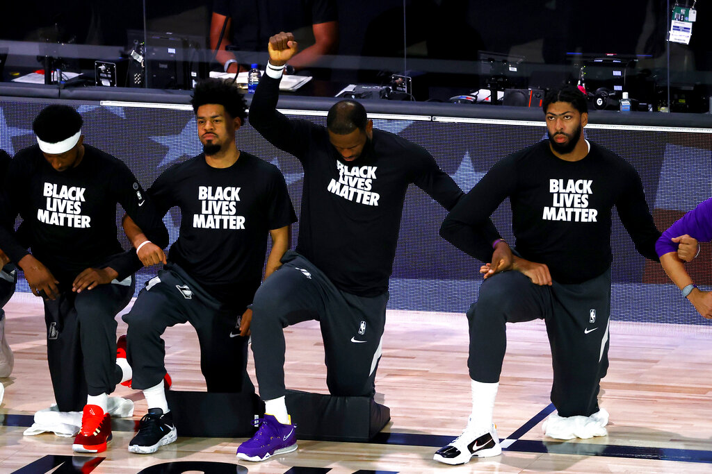 Los Angeles Lakers' LeBron James  kneels during the national anthem prior to the NBA basketball game against the Oklahoma City Thunder Wednesday, Aug. 5, 2020, in Lake Buena Vista, Fla. (Kevin C. Cox/Pool Photo via AP)