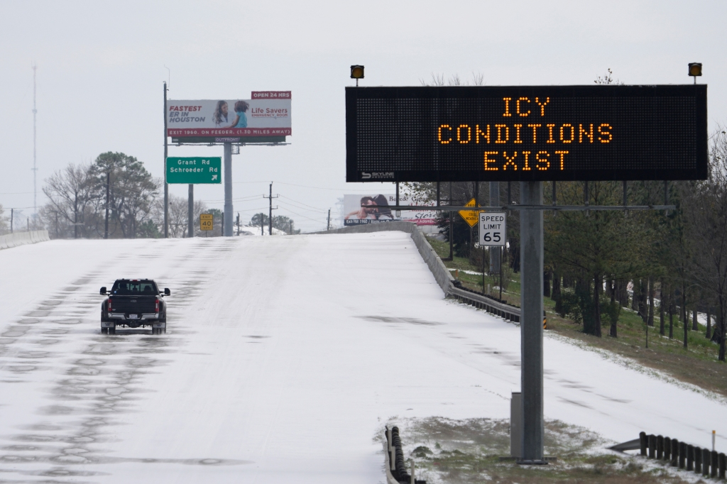 A truck drives past a highway sign Monday, Feb. 15, 2021, in Houston.