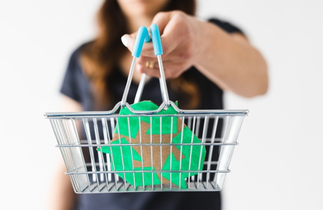 sustainable development and consumer buying habits concept, woman holding a shopping basket with recycle sign towards the camera shot at shallow depth of field