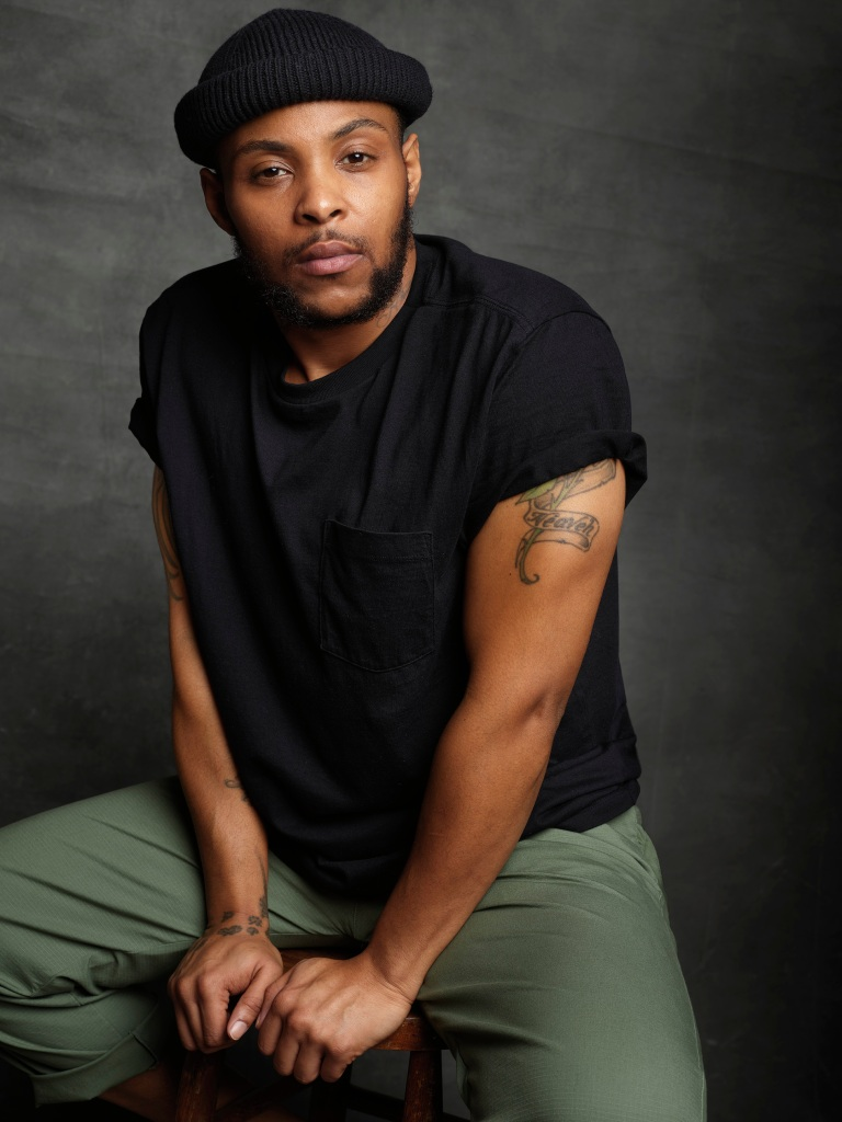 From Gap's campaign, trans community leader D'Jamel Young in a classic black pocket T-shirt, slim pants and beanie.