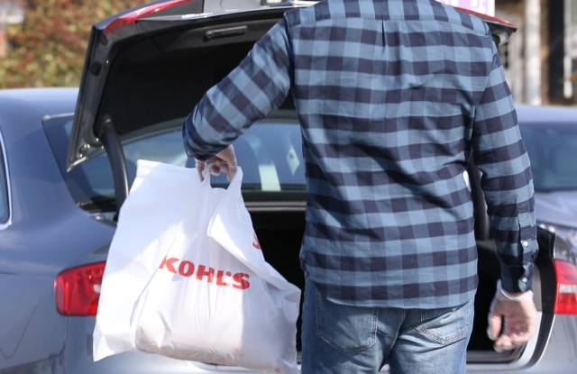 shopper taking kohl's shopping bag to car