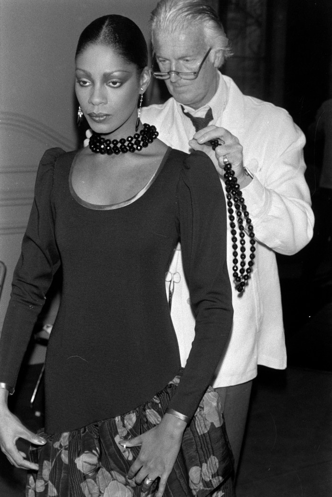 Designer Hubert de Givenchy adjusts a model's look.
