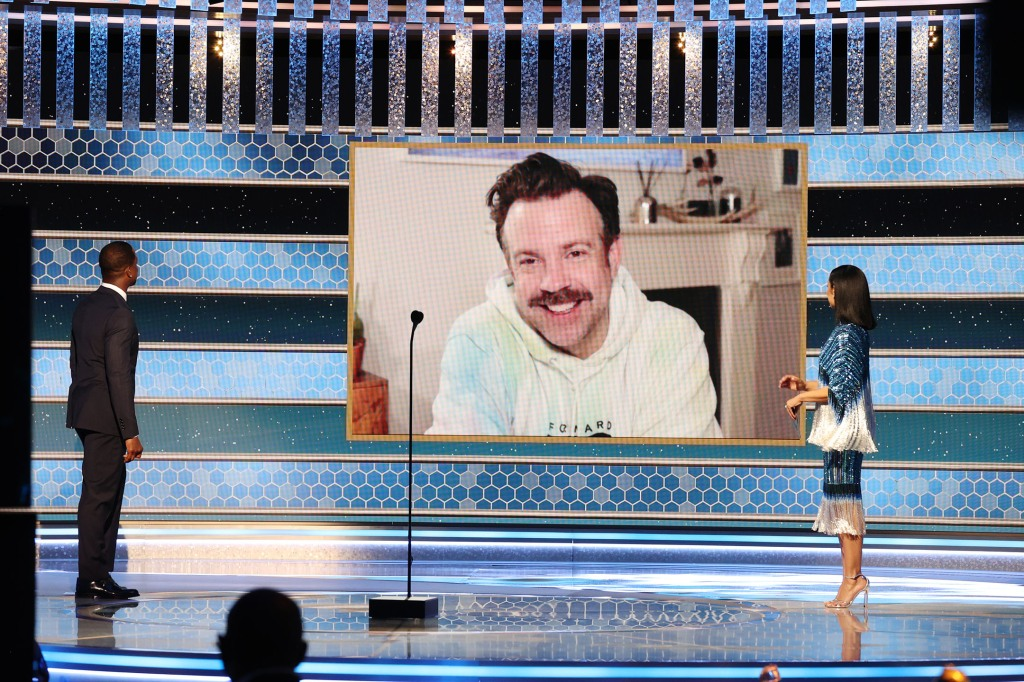 Jason Sudeikis in Listen + Lead Tie Dye Hoodie (c) accepts the Best Television Actor – Musical/Comedy Series award for 'Ted Lasso' via video from Sterling K. Brown (l) and Susan Kelechi Watson.