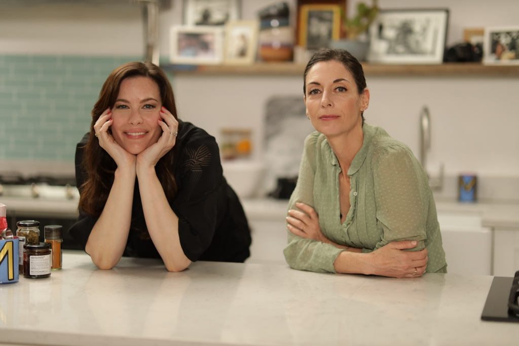Close-up of Mary McCartney and Liv Tyler smiling in the kitchen face in hands