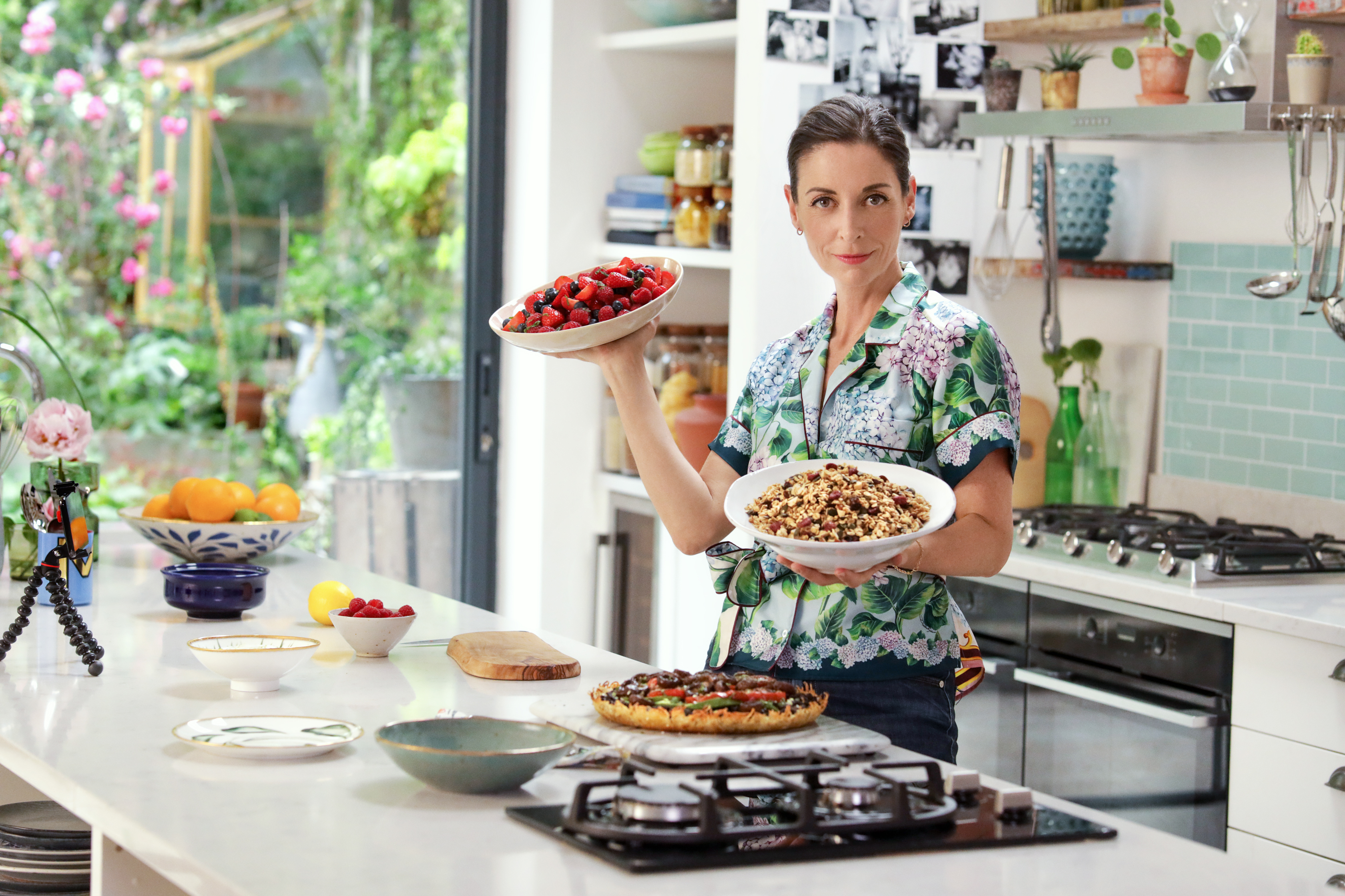 Mary McCartney in Kitchen holding a bowl of Granola Brunch food and smiling to camera