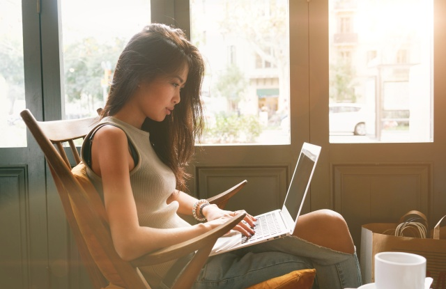 Attractive asian female is typing messages on a laptop while sitting against the wide windows of a coffee shop. a hipster girl is working on a portable computer in a cafe.