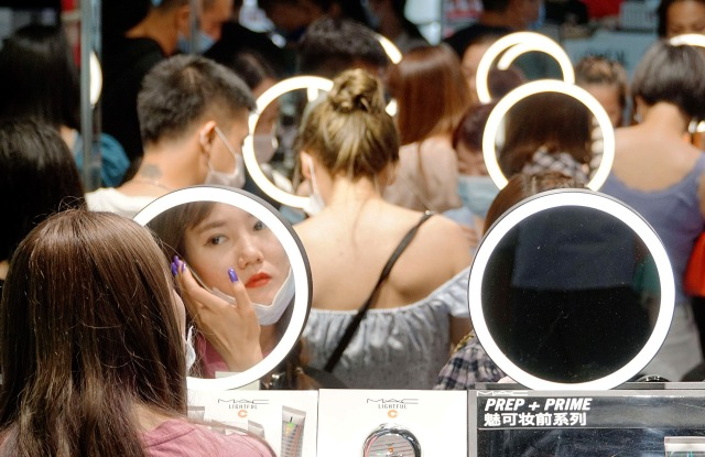 Chinese shoppers trying on beauty products in a duty free shop on Hainan Island, China.