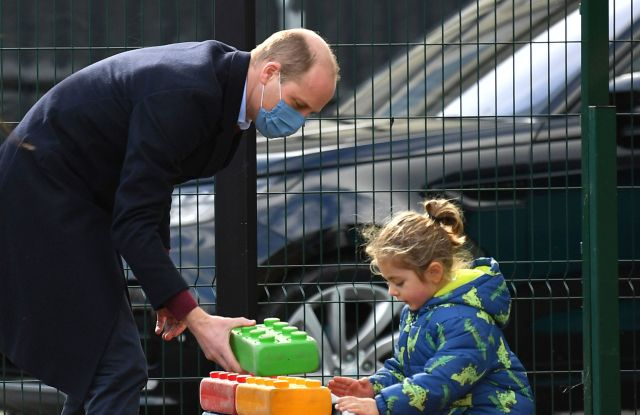 Britain's Prince William plays with a child in the playground during a visit with Kate, Duchess of Cambridge to School21, a school in east London, Thursday March 11, 2021. (Justin Tallis/Pool via AP)
