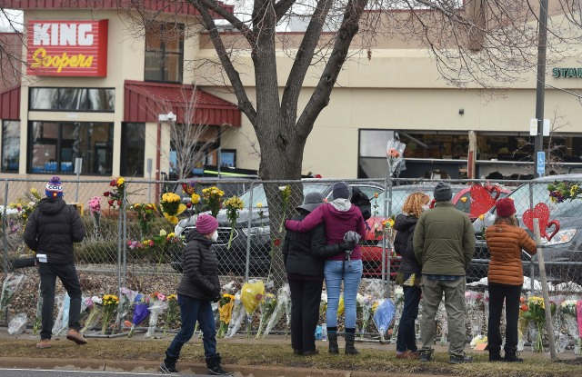 The flowers were growing by the hour on Tuesday, March 23, 2021. They were left by multitudes of mourners for the 10 people killed at the Boulder King Soopers in Boulder, Colo. on Monday. (Jerilee Bennett/The Gazette via AP)
