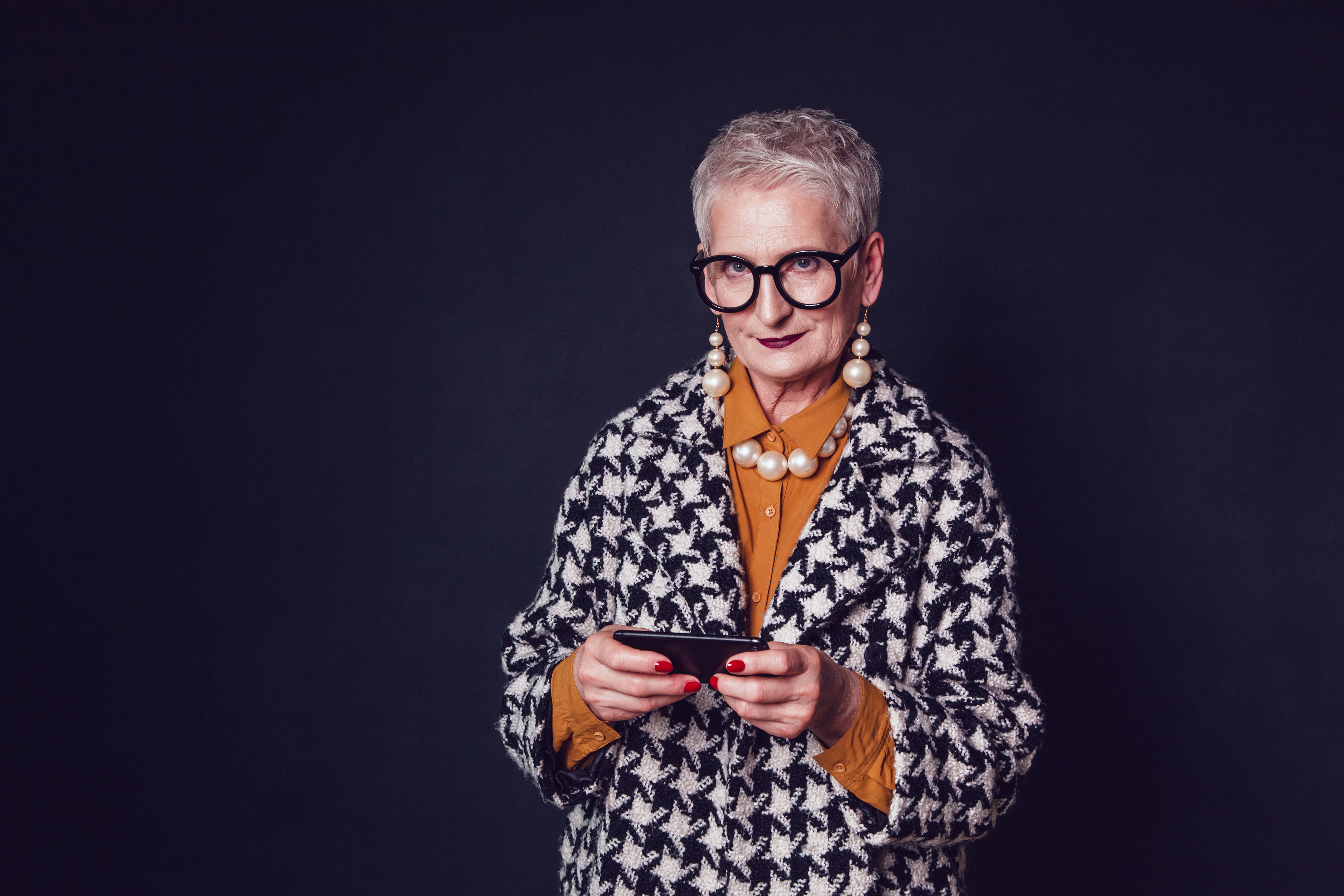 Stylish old woman in glasses using smartphone on a black background.