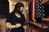 woman in clothing store wearing mask with ipad