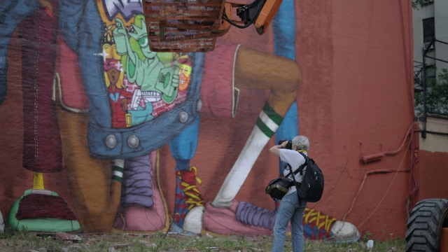 Martha Cooper photographing an Osgemeos mural, in a still from the film.