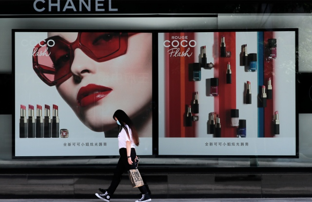 FILE - IN this Thursday, May 28, 2020 file photo, a woman wearing a protective face mask to help curb the spread of coronavirus walks past a Chanel lipstick advertisement billboard in Beijing. Sales of luxury apparel, jewelry and beauty products are set to slide by nearly a quarter this year as the pandemic wipes out more than six years of growth, according to a study released Wednesday, Nov. 18, 2020 by the consultancy Bain.  (AP Photo/Andy Wong, File)
