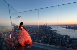 Aeon Elliott models a gown for a fashion shoot while standing on the Edge, an outdoor observation deck overlooking Manhattan, March 2, 2021 in New York. After the virus descended on New York, the only sounds in the streets were wailing ambulance sirens. A year after the pandemic began, the nation's largest metropolis -- with a lifeblood based on round-the-clock hustle and bustle, push and pull -- is adapting and showing new life. (AP Photo/Mark Lennihan)