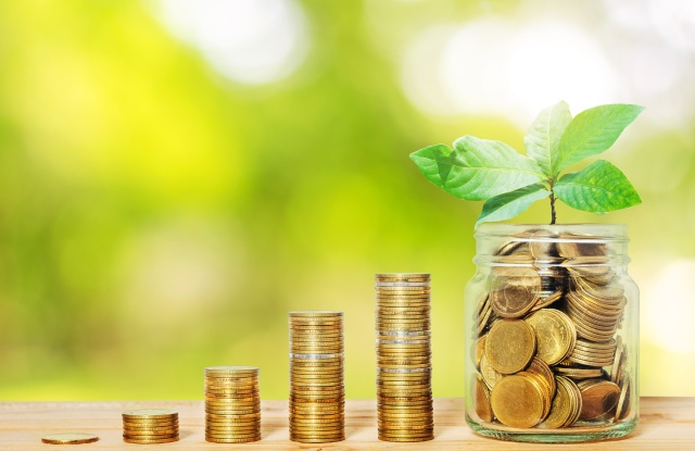 green plant growing up on golden coin in glass jar with money stack on wood table with blur nature background. business financial banking saving concept. investment profit income. startup. successful.